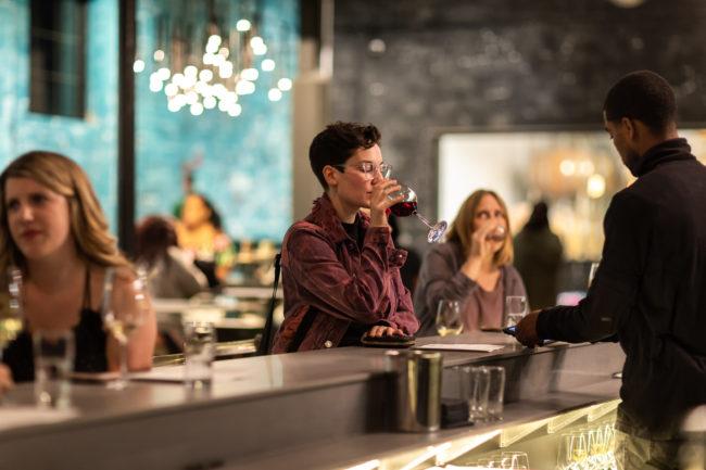 Woman drinking wine at Detroit Vineyards tasting room