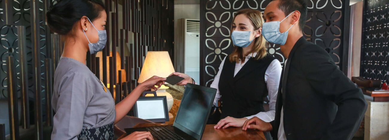 Couple and receptionist at counter in hotel wearing medical masks.